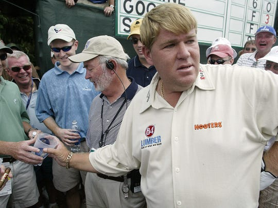John Daly is handed a beer cup that contains his golf ball by patron Rick Best after his ball landed in the cup on the third hole during first round play in the 2005 US Open Championship.