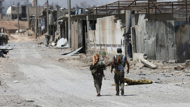 U.S.-backed Syrian Democratic Forces fighters walk past destroyed shops where they fight against Islamic State militants on the front line of the industrial district on the eastern side of Raqqa, Syria, on July 26, 2017.