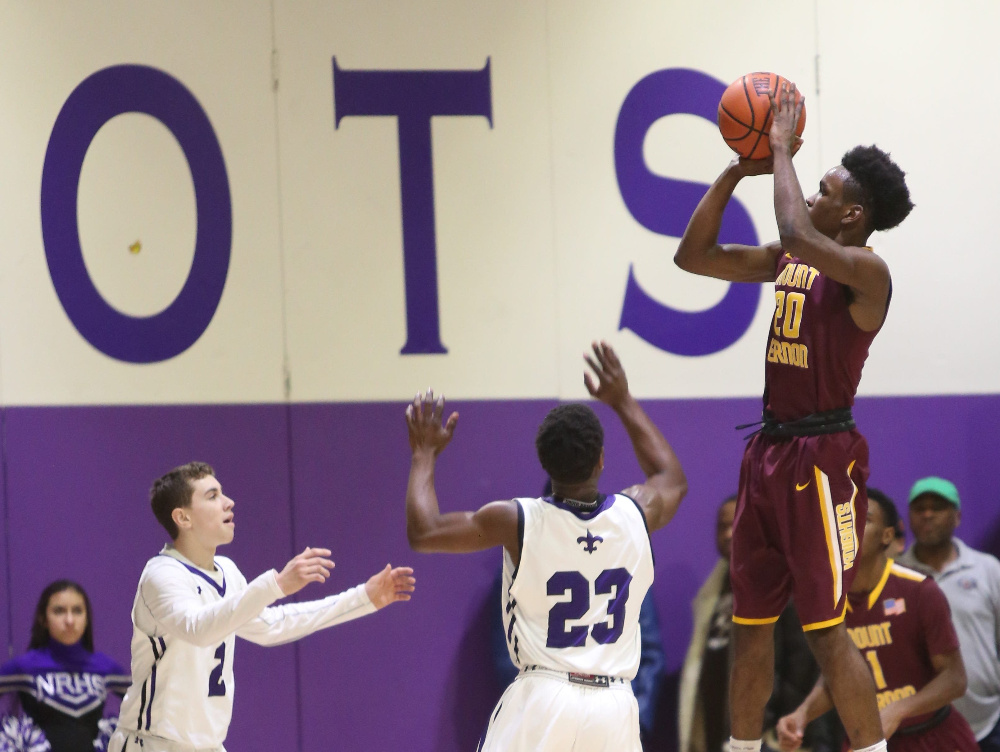 Marco Morency (20) of Mount Vernon goes up for a jump shot over Jake Mieto (2) and Chris Blades (23) of New Rochelle during game action at New Rochelle High School on Jan 4, 2016. Mount Vernon defeated New Rochelle 72-63.