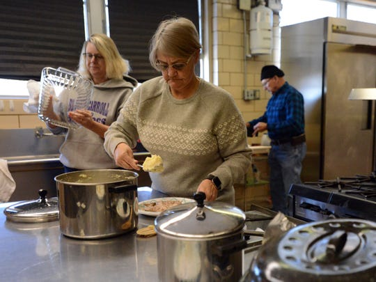 Lisa Carlisle, center, gets food for a client at the warming center at Connexion West Tuesday, Jan. 2, 2018, in Lancaster.
