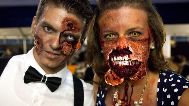 Jeremiah Thomas, left and Cathy Thomas, right, show off their zombie makeup Saturday evening during the Old Town Halloween Zombie Fest's zombie crawl.