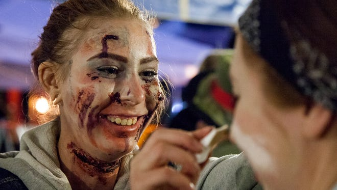 Shii Emde, left, turns Jamie Peake, right, into a zombie Saturday evening under the makeuip tent at the Old Town Halloween Zombie Fest.