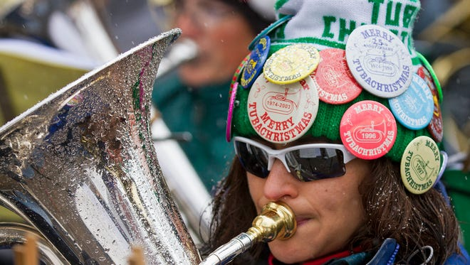 One of ninety-five musicians taking part in the 2015 Tuba Christmas performs as a light snow falls on the Oak Street Plaza in Fort Collins Saturday afternoon.