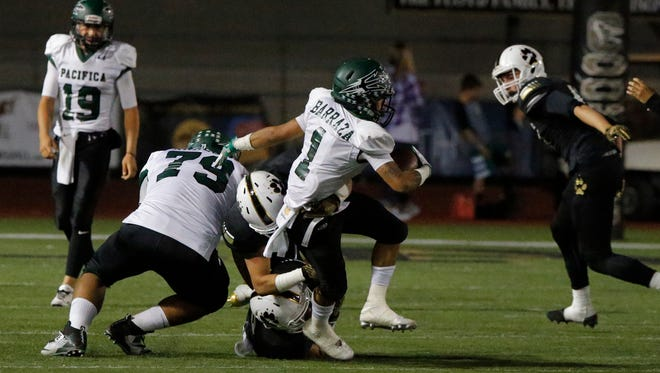 Pacifica''s Adrian Barraza (1) tries to break free of a tackle during the Tritons' loss at Calabasas in Week 3. Pacifica hosts Buena on Friday night.