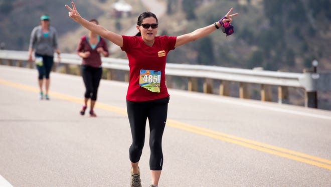 Laura Lacert celebrates nearing the top of the hill on Centennial Drive along Horsetooth Reservoir during the Horsetooth Half Marathon Saturday morning April 23, 2017 in Fort Collins. (Michael Brian/For the Coloradoan)