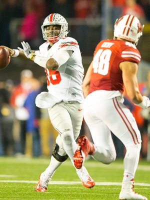 Ohio State quarterback J.T. Barrett throws on the run during Saturday's 30-23 overtime victory at Wisconsin.