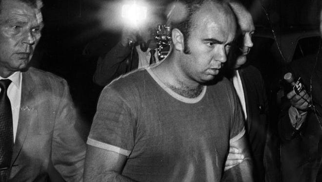 Raymond Kassow, then 24, is led away by police in September 1969. He was one of three men who shot four women during a robbery at Cabinet Supreme Savings & Loan Association in Delhi Township.