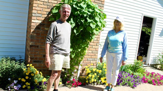 Craig and Susie Burchfield stand on their newly installed walkway that has inspired a variety of flowering plants.