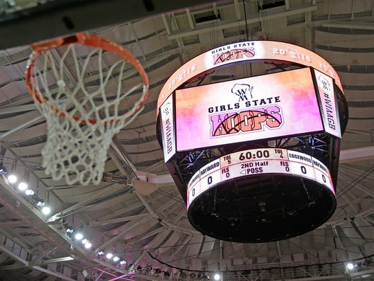 The WIAA girls state basketball logo shines on the Resch Center scoreboard in Ashwaubenon.