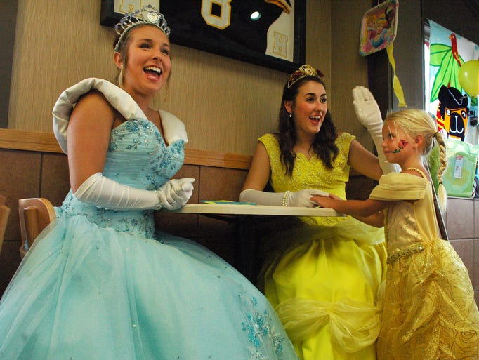 Taylor Hahn, 4, of Gallatin talks to Lily Goodman (right) dressed as Belle from 'Beauty and the Beast'at Wendy's on Monday, July 7, 2014 in Hendersonville during the Princesses and Pirates day. Molly Smith is also shown dressed as Cinderella.