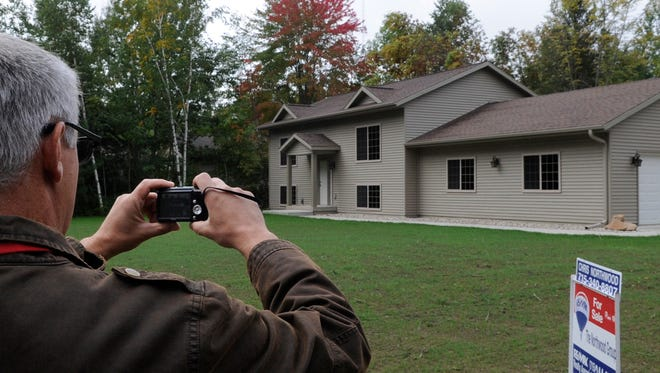 Stevens Point assessor Jim Siebers takes photos of a new home as he prepares an assessment in 2011.