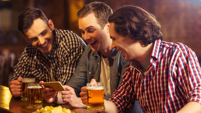 Three young men in casual clothes are talking, using a smart phone and drinking beer while sitting at bar counter in pub
