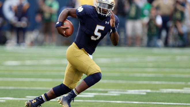 Notre Dame Fighting Irish quarterback Everett Golson (5) runs to the outside against the Rice Owls at Notre Dame Stadium.