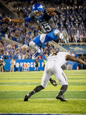 Kentucky Wildcats quarterback Stephen Johnson (15) leaps over Missouri Tigers safety Thomas Wilson (8) for a 7 yard gain during the game at Kroger Field on the campus of the University of Kentucky in Lexington, Saturday, Oct. 7, 2017.