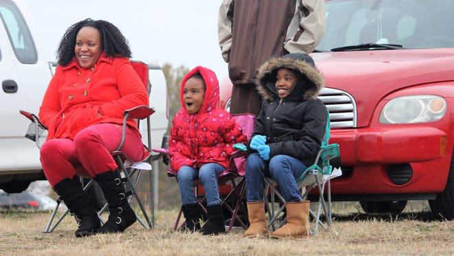Nevaeh Jackson, 5, center, watches horses pass by Sunday at the Anderson County Christmas Parade alongside her sister, 8-year-old Skye Grissom and mother, Kimberly Jackson.