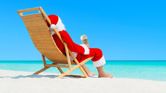 Christmas Santa Claus resting on wooden deckchair with fresh orange juice cocktail at ocean sandy tropical beach - New Year travel destinations  in hot countries concept