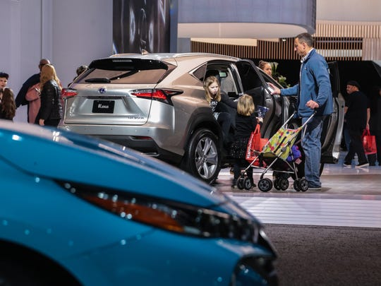 (right to left) Dale Wagnitz, of Royal Oak and his daughters Lily Wagnitz and Addison Wagnitz look over a Lexus NX 300h vehicle on Tuesday January 17, 2017 during the 2017 North American International Auto Show at Cobo Center in Detroit.