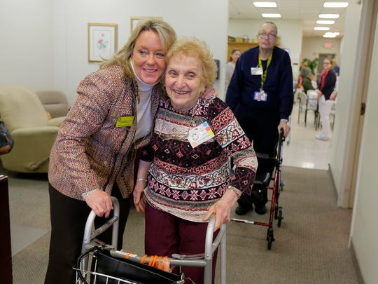 Tracey Wolfman spends time with Angie Eagone, 85, of Middletown at We Care Adult Care Inc. in Middletown.