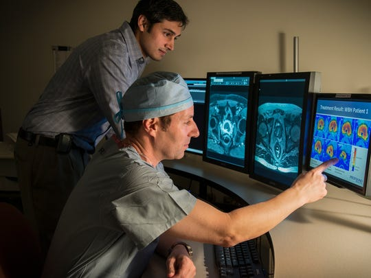 James Relle, M.D. (seated), Beaumont Health urologist and principal investigator, with radiologist and sub-investigator, Kiran Nandalur, M.D. Relle is using a new tool that kills prostate cancer cells with heat, guided by MRI.