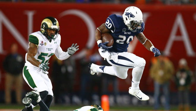 Nevada Wolf Pack running back James Butler (20) leaps over a Colorado State Rams defender in the third quarter Arizona Bowl at Arizona Stadium. Nevada defeated Colorado State 28-23.