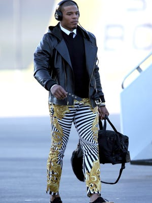 Carolina Panthers quarterback Cam Newton walks after exiting a plane during team arrivals at the Mineta San Jose International Airport in preparation of Super Bowl 50 against the Denver Broncos.