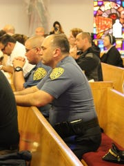 Lt. Mark Fiorentino (front) and Patrolman Charles Sbarra III pray during the Blue Mass at St. Joseph's Church.