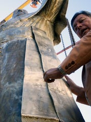 Sculptor Pedro Francisco Rodriguez puts the final touches on the bronze statue of Pope Francis.