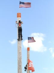 Tyler Alden and Trask Hill scale 40-foot poles during the Timberworks Lumberjack Show at the Richland County Fair on Tuesday afternoon.