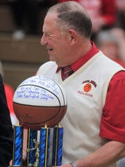 Holmes head coach Mike Listerman, who is retiring at the end of this season, was given a commemorative trophy by the Covington Catholic administration honoring his long tenure with the Colonels, during the 35th District tournament Feb. 21, 2018 at Holmes.