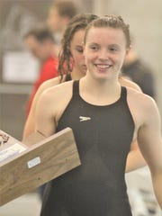 Dixie Heights senior Mallory Beil is all smiles with the team trophy during the KHSAA state swimming and diving championships Feb. 24, 2018 at the University of Louisville.