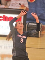 """St. Henry senior Bridget Bessler sets the ball during the All """"A"""" Classic 9th Region volleyball tournament August 27, 2018 at Holy Cross gymnasium. St. Henry beat Newport Central Catholic and Holy Cross 2-0 to win the title."""