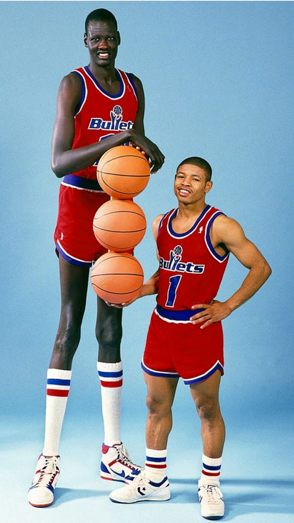 Here's a picture of the tallest and shortest players in NBA history standing next to each other