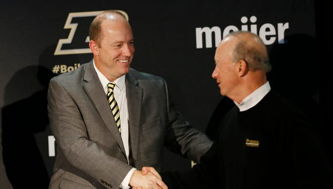 Jeff Brohm shakes hands with President Mitch Daniels after being named head football coach Monday, December 5, 2016, at Purdue University. The former Western Kentucky football head coach replaces Darrell Hazell, who was fired six games into the season.