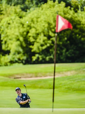 Matt Benson hits to the 14th green during the All-City Golf Tournament Sunday at the Eagle Eye Golf Course in East Lansing.