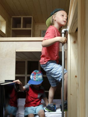 In this July 16, 2016, photo, Drake Darger, right, and Aiden Garder, play in a model tiny house at a display outside the Cabela's in Lehi, Utah. The Tiny Home movement is a worldwide change in the way people use their living spaces. The Daily Herald reports it is becoming a trend in Utah County. (Chris Samuels/The Daily Herald via AP)