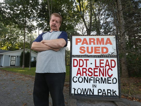 John Chart alongside a sign he placed at the end of his driveway in Parma. (May 2010 photo).