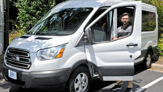 Sean Lally, youth prevention specialist at OneEighty, stands with a new van purchased to provide transportation services to clients. The van will take them to their appointments at either OneEighty or ANAZAO Community Partners.