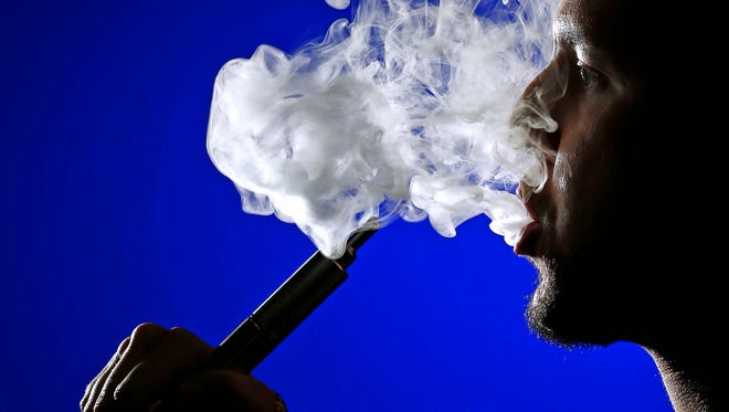 """Matt Berger, owner of e-cigarette retailer """"Butt Out,"""" exhales a cloud of vapor. As Arizona lawmakers face a budget shortage, should they consider taxing e-cigs like tobacco cigarettes?"""