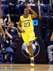 Caris LeVert of the Michigan Wolverines celebrates against the Illinois Fighting Illini on March 14, 2014 in Indianapolis.