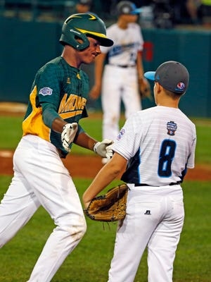 Walla Walla, Wash., third baseman Hayden Lomeli (8) greets Sioux Falls, S.D.'s Marcus Phillips, left, as he rounds third after hitting his second solo home run, off pitcher Andrew Hill, center, in U.S. pool play at the Little League World Series baseball tournament in South Williamsport, Pa., Saturday, Aug. 19, 2017. Washington won 4-3. (AP Photo/Gene J. Puskar)