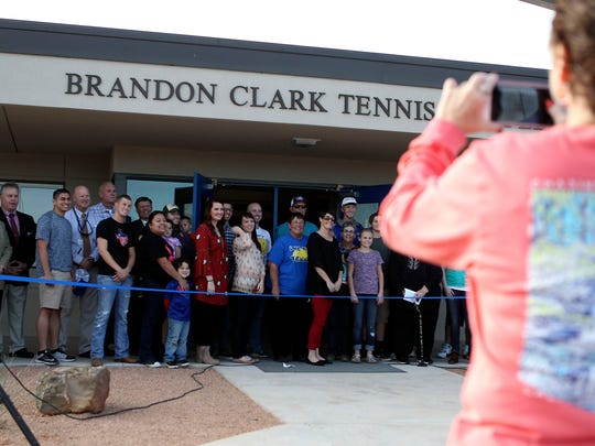Family, friends and former students of tennis Coach Brandon Clark take a photo in front of the new tennis complex at Lake View High School that was dedicate in Clark's honor Monday, Nov. 21, 2016.