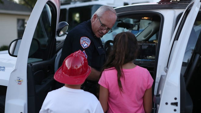 Officer Steven Quade chats with children while showing them the inside of his police cruiser during the annual National Night Out event held at Solid Rock Church Tuesday, Oct. 3, 2017.