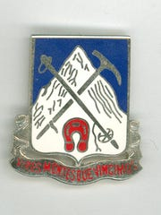 87th pin: In front of a mountain background the pin features a ski pole, ice axe and mule shoe. This is the only officially recognized regimental pin. The men of the 85th and 86th rejected the Army's official version and adopted these designs to represent their actual duties and accomplishments.
