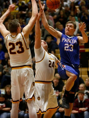 Parker's Connor Carlson, right, tries to shoot as he drives the baseline against Langford Area's Zac Fries (24) and Mason Larson (23) during Thursday's opening round game at the South Dakota Class B boys basketball tournament at Wachs Arena.