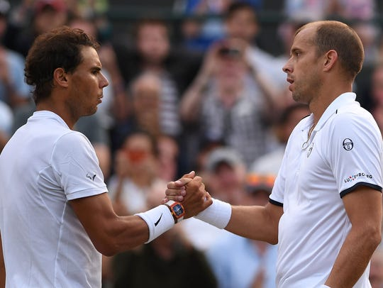 Gilles Muller (right) shakes hands with Rafael Nadal