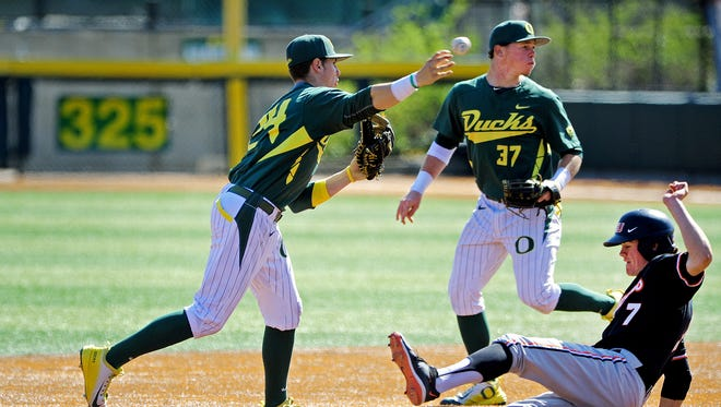 Oregon shortstop Mark Karaviotis (24) gets a force out on Oregon State's Trever Morrison and turns a double play at PK Park, on Sunday, April 12, 2015, in Eugene. Oregon won the game 10-9.
