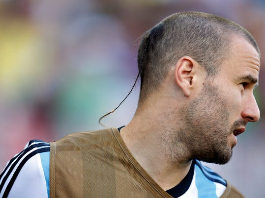 FILE - In this July 1, 2014, file photo, Argentina's Rodrigo Palacio warms-up on the touchline during the World Cup round of 16 soccer match between Argentina and Switzerland at the Itaquerao Stadium in Sao Paulo, Brazil.  Palacio with his shaved head except for a rat's tail at the back, arguably has the most jaw-dropping haircut at the World Cup. (AP Photo/Frank Augstein, File)