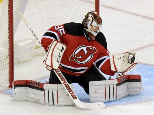 New Jersey Devils goaltender Cory Schneider gloves the puck during the third period of an NHL hockey game against the Minnesota Wild, Saturday, Oct. 22, 2016, in Newark, N.J. (AP Photo/Bill Kostroun)