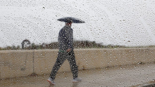 A man gets in his exercise along Wollaston Beach, Quincy from under an umbrella on Wednesday, Oct. 28, 2020. Greg Derr/ The Patriot Ledger