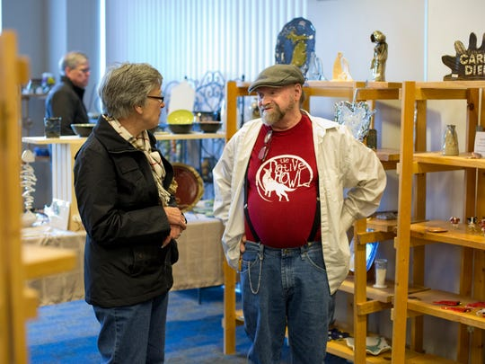 Potters Jane Barden, of St. Clair Township, and Mark Brant, of Port Huro, talk during the Potters Market. The St. Clair County Community College 16th annual Potters Market is Nov. 15-18.